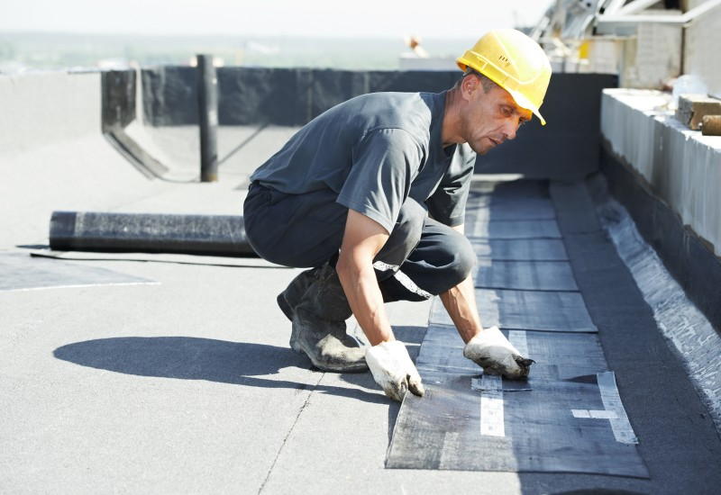 Roofer preparing part of bitumen roofing felt roll for melting b
